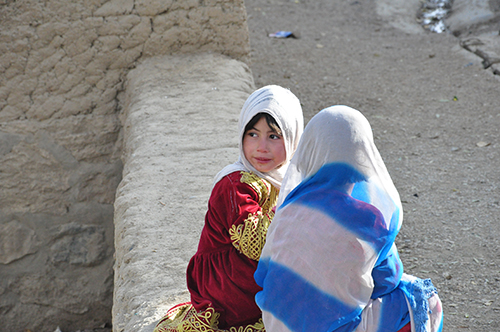 Afghan girls sitting on stone wall in Bamyan